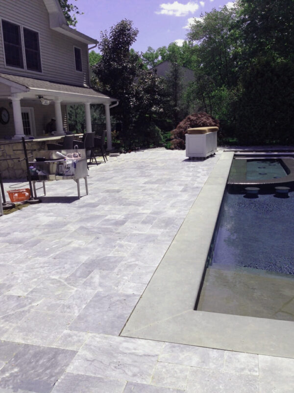 pearl grey limestone unfilled and tumbled pavers around pool